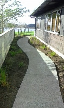 a gently curved exposed aggregate path with native planting and timber fence
